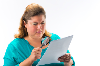Frau versucht, kleingedrucktes im Handyvertrag zu lesen.