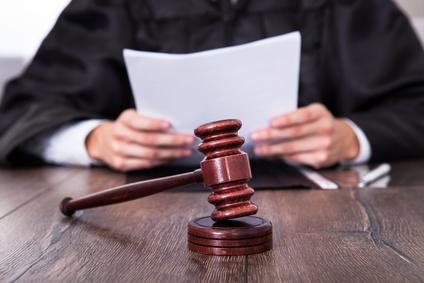 Richter sitzt mit Dokumenten am Tisch
