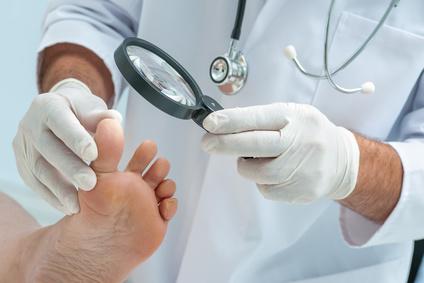 Arzt untersucht den Fuß einer Patientin