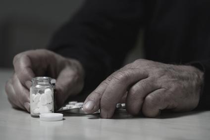 Mann mit mehreren Tabletten vor sich