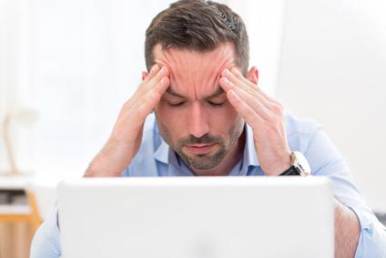 Frustrierter Mann sitzt am Laptop