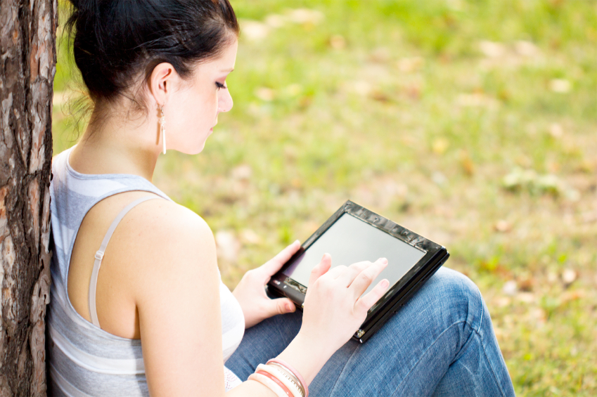 Frau im Grünen mit einem Tablet auf dem Schoß