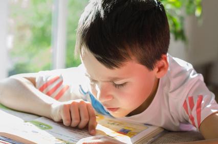 Kleiner Junge sitzt am Tisch und lernt