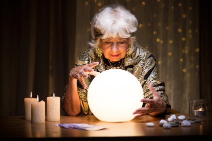 Wahrsagerin sitzt mit Kristallkugel am Tisch