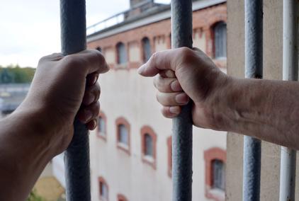 Hände an einem Fenster im Gefängnis